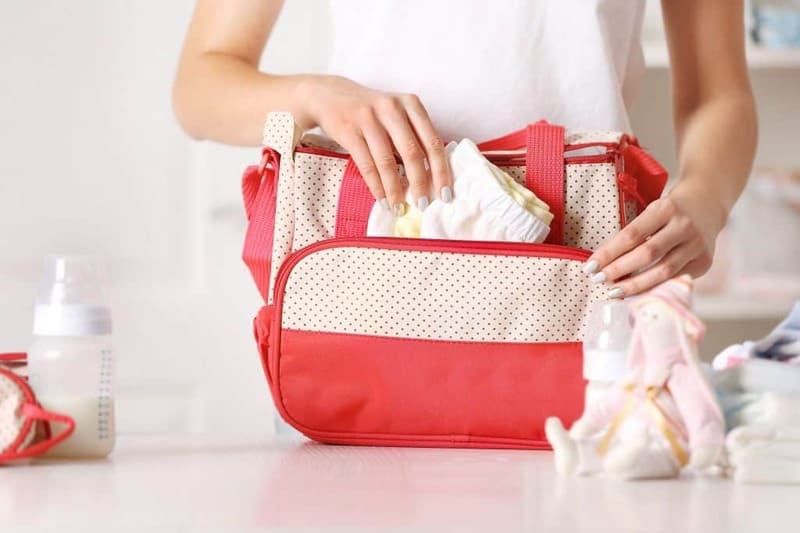 bigstock-Woman-packing-her-bag-with-chi-157830569-1024x682