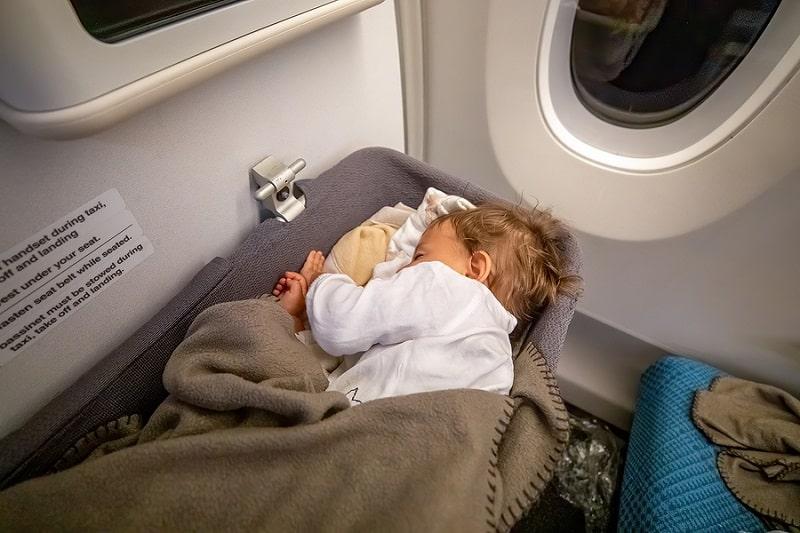 baby sleeping on plane bassinet