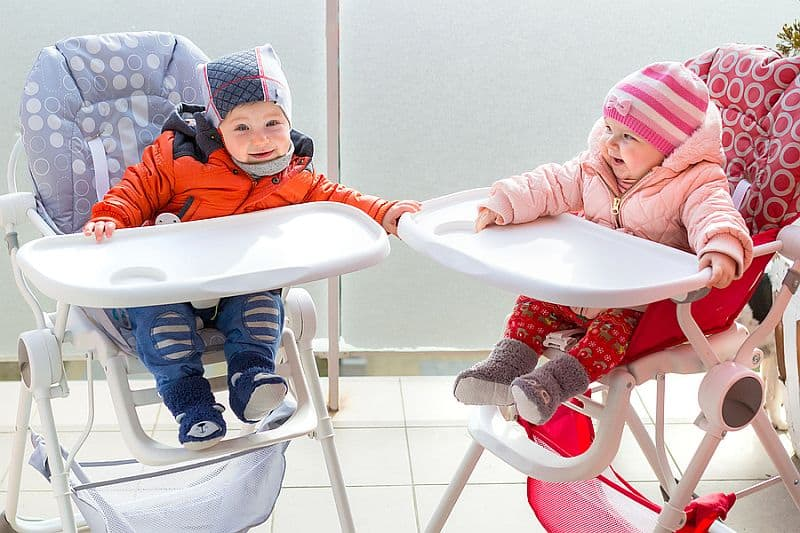 Baby boy and girl twins sit on the high chairs
